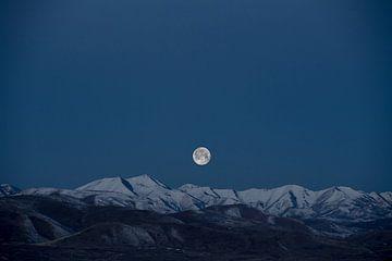 Volle maan boven besneeuwde bergtoppen van Roger VDB