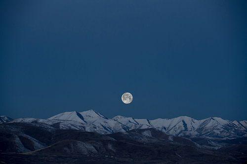 Volle maan boven besneeuwde bergtoppen van