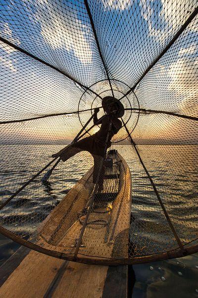 Visser die met traditionele boot op het Inle meer in Myanmar op ouderwetse wijze met een vis korf vi