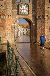 Doorkijkje van de Koppelpoort in Amersfoort met een jogger op de voorgrond.