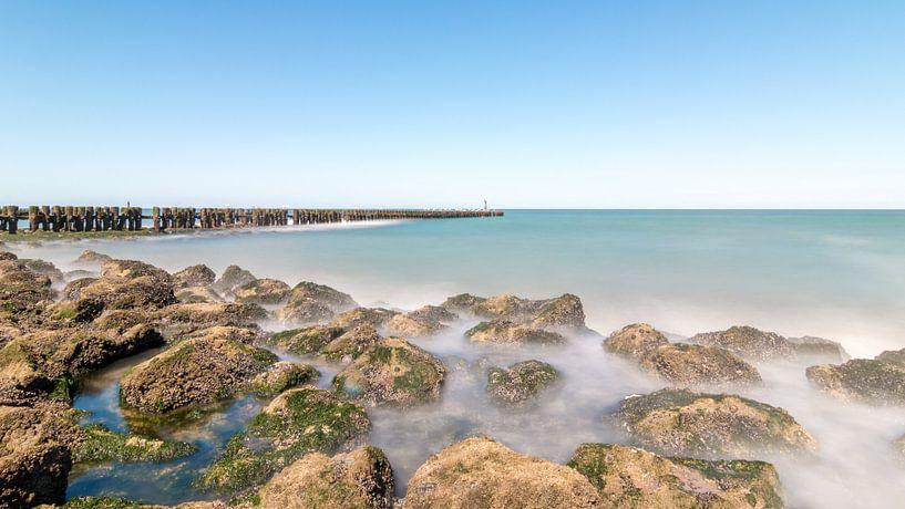 Stromend water van de zee rondom stenen op het strand van Josephine Huibregtse