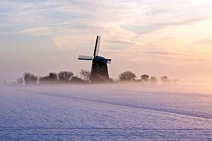 Ouderwetse molen in de besneeuwde velden bij zonsondergang
