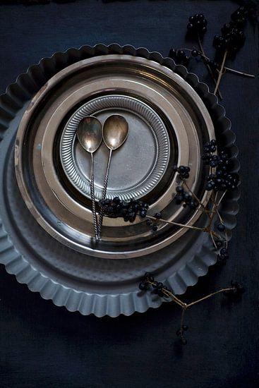 zilveren lepeltjes met tinnen bordjes en springvormen op een donkere achtergrond van Beeldig Beeld