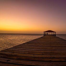 Geel met paarse zonsondergang op de pier aan het strand van Reis Genie