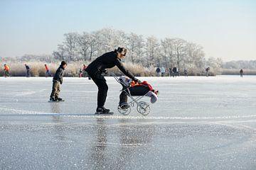 Moeder met kind in kinderwagen op het ijs von