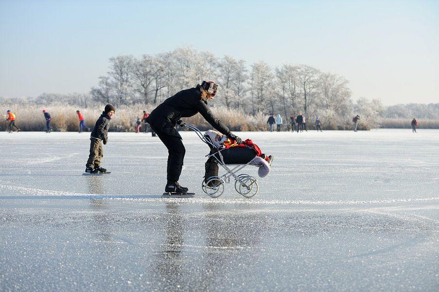Moeder met kind in kinderwagen op het ijs