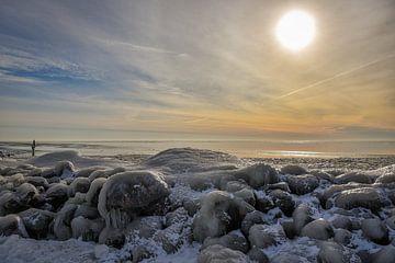 Een dicht gevroren IJsselmeer met ondergaande zon. van Bert de Boer