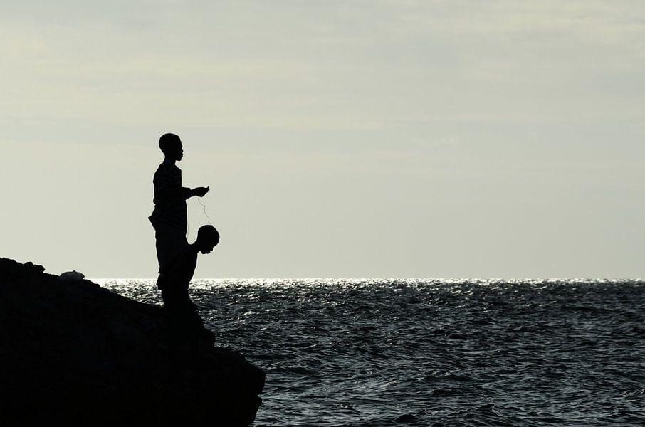 Jongen op rotsen aan het vissen