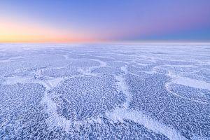 Mooie structuren op een met ijs bedekt IJsselmeer tijdens de winter. Aan de horizon komt de zon lang van Bas Meelker