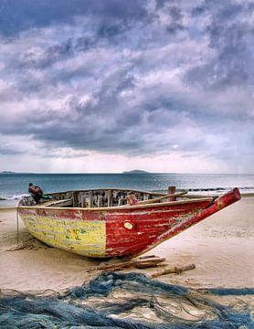 Rode en gele houten vissersboot op leeg tropisch strand van Tony Vingerhoets