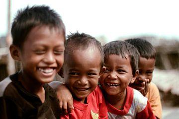 Lachende Indonesische kinderen in vissersdorp van André van Bel