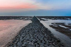 Drooggevallen pier in de Waddenzee bij zonsondergang.