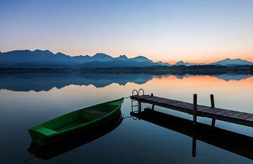 Boot aan de steiger met alpenpanorama in de zonsondergang
