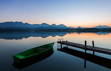 Boot am Steg mit Alpenpanorama im Sonnenuntergang