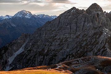 Hiken in de alpen in de herfst. Een stelletje loopt samen een berg op van Hidde Hageman