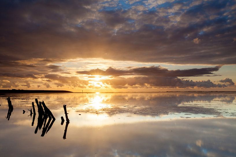 Gouden zonsondergang op het wad van Ron Buist