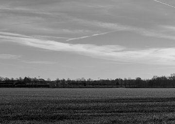 Weite Aussicht auf die Landschaft. Schwarz und weiß mit einem Flugzeugstreifen am Himmel. Am Horizon von Lieke van Grinsven van Aarle