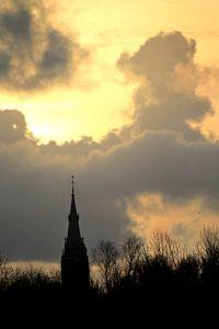Spire of Delft against a yellow sky van