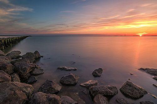 Rotsen in zee, tijdens een prachtige zonsondergang bij Holwerd