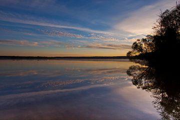 De dageraad over het rustige wateroppervlak van het meer. De ochtendblauwe hemel wordt verlicht door van Michael Semenov