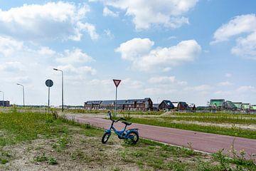 kleines Fahrrad auf der roten Straße, das einsam steht von Lieke van Grinsven van Aarle