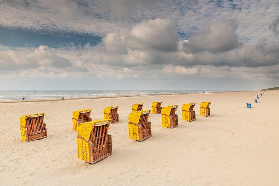 Gele strandstoelen op een herfstig strand