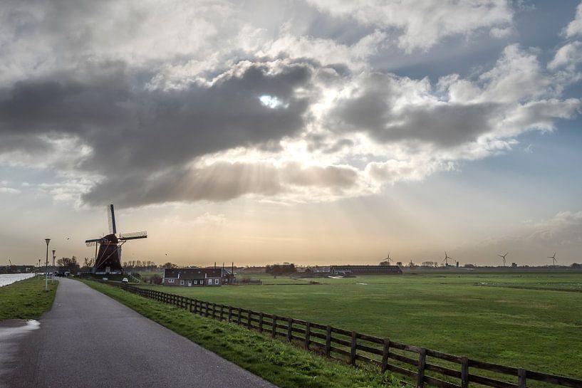 Polderlandschaft mit Windmühle unter einer Wolke mit Sonnenharfe von Rob IJsselstein