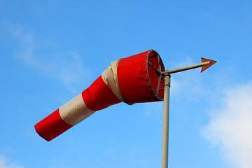 Roodwitte windwijzer in de volle wind met een blauwe lucht als achtergrond van