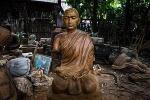 Houten Budha beeld in achtertuin van dump
