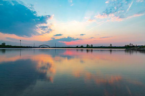 Buntes Abendlicht, das sich im Wasser spiegelt und nach Sonnenuntergang leuchtet.