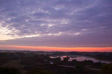 Zonsopkomst boven duinen met kleurrijke wolken van Menno van Duijn