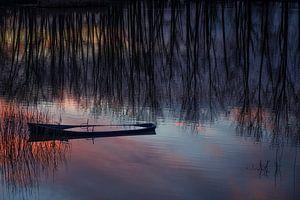 Half gezonken bootje tijdens zonsondergang.