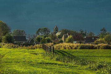 Het Friese dorpje Lichtaard in de nazomerzon met een donkere lucht op de achtergrond van Harrie Muis