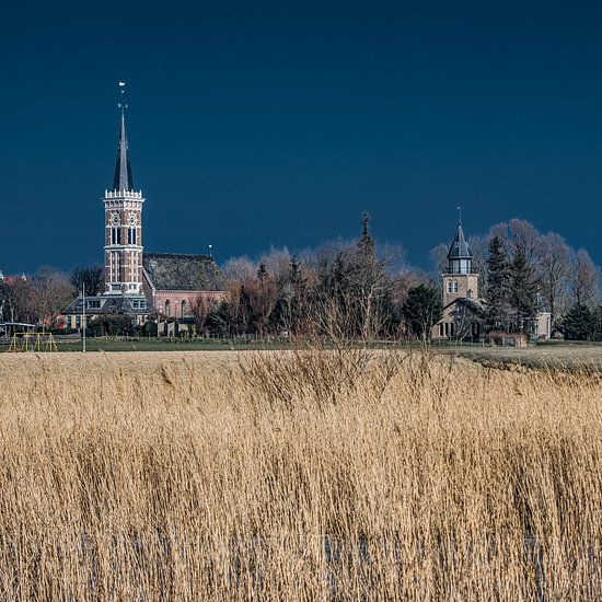 Het Friese dorpje Cornwerd met droog riet op de voorgrond. van Harrie Muis