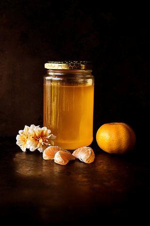 Topf mit Honig und Clementinen