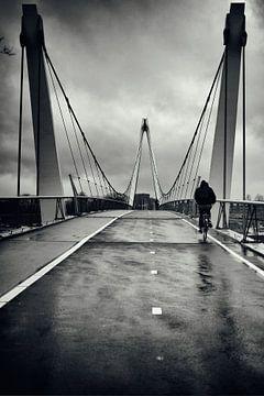 Straatfotografie in Utrecht. De eenzame fietser in de regen op de Dafne Schippersbrug in zwart-wit.  van De Utrechtse Grachten