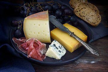 Eetbordje met diverse kaassoorten, luchtgedroogde ham, blauwe druiven en brood op donker rustiek hou van Maren Winter