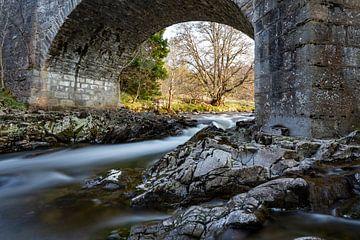 Kleine waterval onder een stenen brug - Schotland van Remco Bosshard