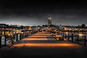 Iemand kijkt naar Deventer tijdens het blauwe uur aan de IJssel in zwart wit