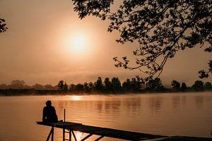Une femme est assise sur un échafaudage au lever du soleil