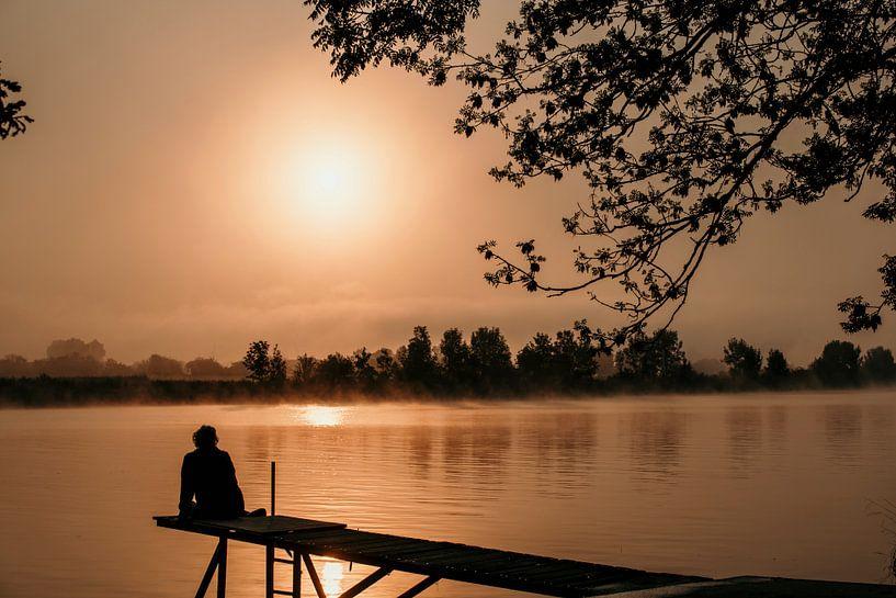 Une femme est assise sur un échafaudage au lever du soleil sur ChrisWillemsen