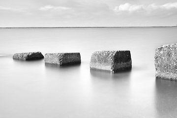 Betonblokken die de zee in lopen von Jan van der Vlies