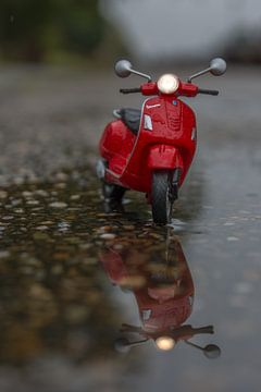 Miniatuur Vespa scooter in de regen en reflectie van John van de Gazelle