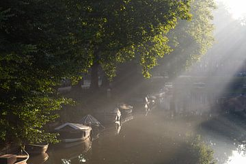 De zon breekt door en schijnt op de boten in de singel van Utrecht van Michel Geluk