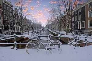Besneeuwd Amsterdam in Nederland in de winter bij zonsondergang van