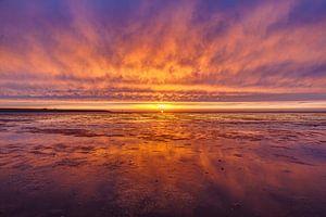Vurige zonsondergang boven het wad van