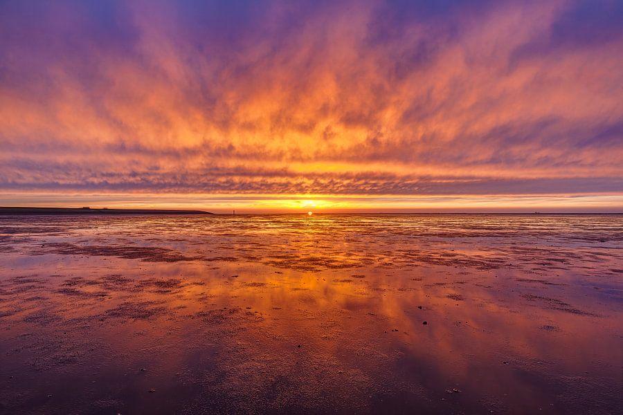 Vurige zonsondergang boven het wad