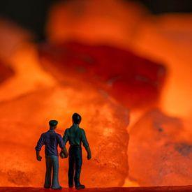 Mannen samen hand in hand kijkend naar het oranje vuur in stenen van JM de Jong-Jansen