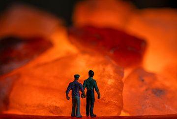 Männer zusammen Hand in Hand mit Blick auf die orange Feuer in Steinen von JM de Jong-Jansen