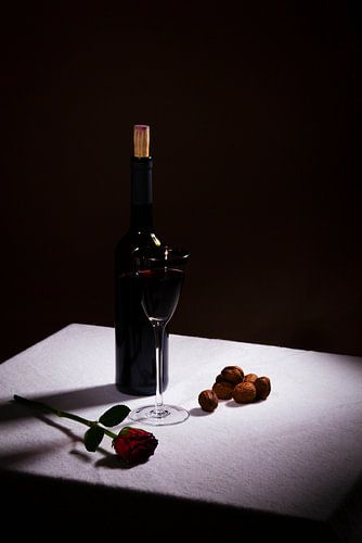 Stilleven met rode wijn en rode roos